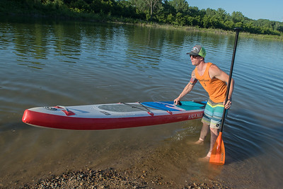 Dan Lee takes his paddle board out of the water while assisting a paddle boarding yoga class put on by Bent River. Lee plans to paddle board the entire length of the Mississippi River starting on August 31. Photo by Jackson Forderer