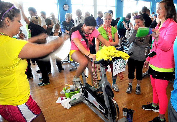 Alicia Reyes gets some help from her teammates as she rides a stationary bike during Pedal Past Poverty, a fundraiser for Partners for Affordable Housing, Saturday at the Mankato YMCA.