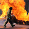 An instructor walks past a simulated propane tank fire during a training exercise.