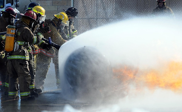 A fireman reaches through a cone of water to turn off a propane tank during an exercise.