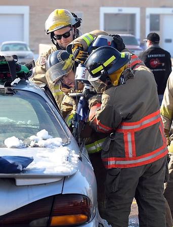 Firemen use a pneumatic tool to remove the door on a car during an extrication exercise.