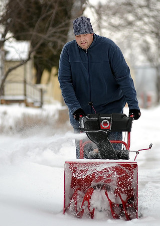 Jason Bobby clears snow Monday morning from the first round of snow storm Saturn. The forecast called for snow to resume Monday night, continuing through today, putting much of the state under a winter storm warning.<br /> <br /> John Cross