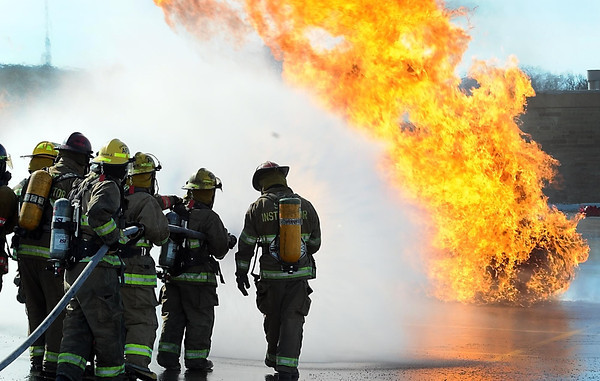 An instructor guides a fire crew through putting out a propane tank fire.
