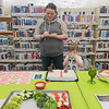 Ann Dempster fills out her voting card while Lyle Dempster, 4, enjoys the punch given out by the Taylor Library in North Mankato during the Edible Book Festival. The People's Choice Award for the adult category went to Michael Borglum for a cake resembling a tree stump after the book Hatchet by Gary Paulsen. Photo by Jackson Forderer