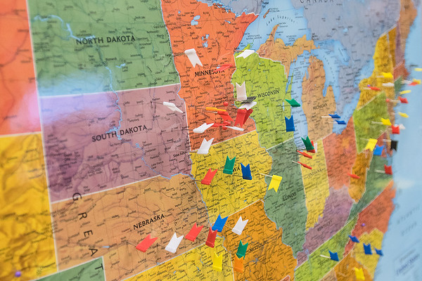 a map with flags and pins, showing everything from NFL teams down to high school teams, at the Kato Collar office Photo by Jackson Forderer