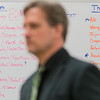 stands in front of a white board with the categories of opportunities and threats noted on it Photo by Jackson Forderer