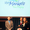 Anna Thill, president of the Convention and Visitors Bureau — now to be known as Visit Mankato — speaks at the Greater Mankato Growth annual meeting Thursday. Behind her is Jonathan Zierdt, president and CEO of GMG, and Eric Harriman (left), coordinator of City Center Partnership.