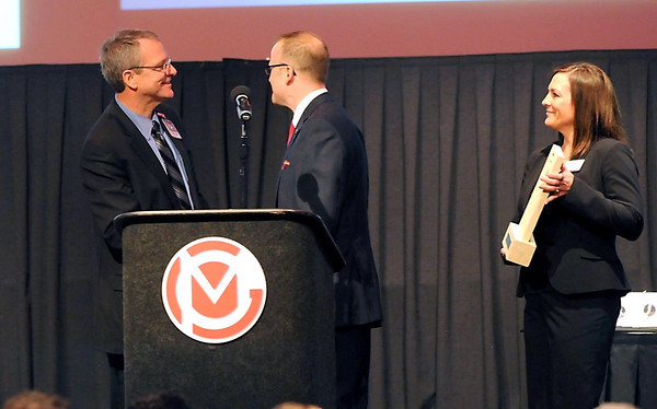 Dr. Greg Kutcher (left) receives congratulations from Greater Mankato Growth President and CEO Johnathan Zierdt for Kutcher's three years as chair of the GMG board. GMG gave Kutcher an award for his service during the GMG annual meeting on Thursday, which is held by GMG's Karen Tost.