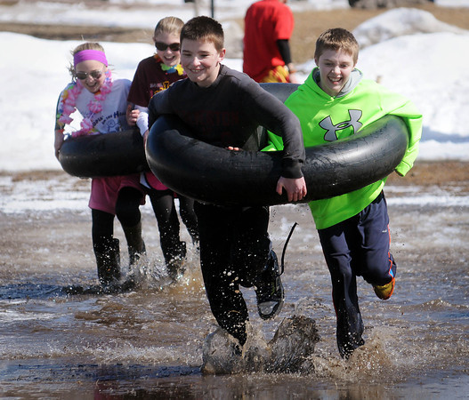 Garfield Elementary sixth graders splash through the thawed Wheeler Park rink during a relay race that was part of pond games on Thursday.