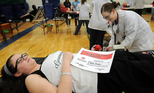 Maple River High School tenth grader Maria Reeves is tended to by Brenda Smith, a collection specialist for the Red Cross, as she donates blood for the first time on Thursday.