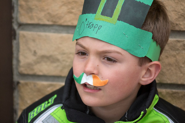 Brayden Trapp, 8, dons an Irish flag mustache and watches the St. Patrick's Day parade along Minnesota Street in New Ulm. Brayden's mother Tiffany Trapp said they traveled from Springfield to see the parade. Photo by Jackson Forderer