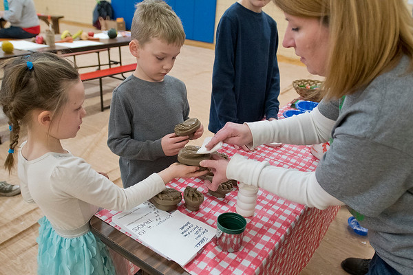 Jill Gartner, right, helps Aaliyah Hulke, 6, and Augusten Abraham, 6, prepare their animal track molds to be placed into plaster cast at the Re-Skilling Festival held at Lincoln Community Center on Saturday. The festival taught people skills to create things on their own, from musical spoons to artisan bread. Photo by Jackson Forderer