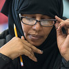 "Halimo Mohamed adjusts her glasses while reading during a citizenship class at Lincoln Community Center. Teacher Tom Tacheny said, ""I have some Hispanics who are really worried,"" and noted the difference between immigrants who have to work and refugees who receive aid. Photo by Jackson Forderer"