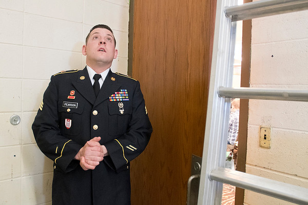 Sgt. Dustin Pearson waits behind a closed door to surprise his mother, Margaret Pearson, as she graduated as a registered nurse through Rasmussen College. Dustin was last stationed in Kuwait before coming home for the surprise. Photo by Jackson Forderer