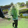 Penny Gorman, 8, gets doused with green powder by Chuck Schoettler as she made her way around Spring Lake during the Monroe Color Run. Photo by Jackson Forderer