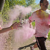 A runner in the Monroe Color Run gets pink powder thrown his way at one of four coloring stations. Photo by Jackson Forderer