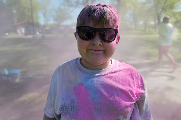 "Calvan Hunt, 8, a Monroe Elementary student, stops for a portrait as he and other students used the remaining pink powder used during the Color Run. Calvan said that he didn't just have many colors on him but exclaimed, ""I am color!"" Photo by Jackson Forderer"