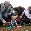 Colton Hartman, 1, puts Easter eggs into his father Josh's hat during an Easter egg hunt Saturday at Dakota Meadows Middle School.