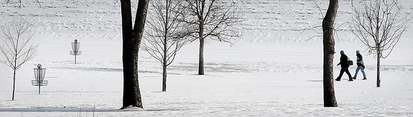 John Cross<br /> Disc golfers play a round at snow-covered Land of Memories Park. By this time a year ago, conventional golf courses already were expanses of green and open for business after record warm temperatures during the month of March.