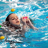 Easter eggs float around Josie White, 9, as shee looks inside one during an Easter egg hunt in the New Ulm Recreation Center's pool Friday.