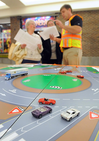MnDOT's Brett Benzkofer explains how a roundabout works to a pair of visitors to a booth Saturday at the River Hills Mall. Pat Christman