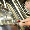 Pat Christman <br /> Manakto Brewery co owner Tim Tupy taps a sample of the brewery's mint stout beer from a tank at the brewery.