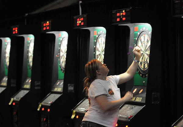 A player checks the score before removing her darts during the C&N Sales dart tournament Saturday at the Verizon Wireless Center. Photo by Pat Christman