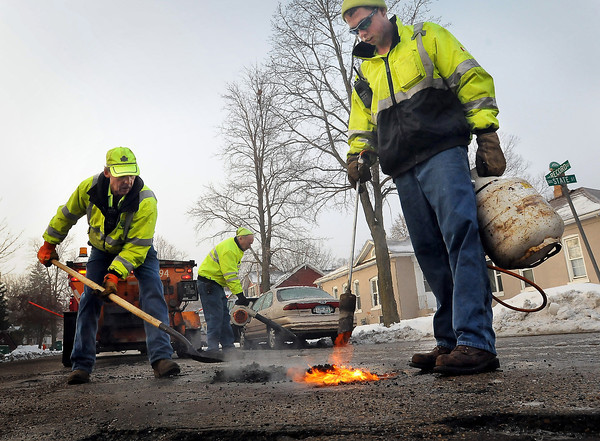 Mankato Street Department employees (from left) Perry Braam Gary Otto and Ryan Thormodson fill in a crop of  potholes at the intersection of State and Record Streets.