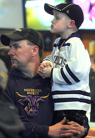 Riley Beske, 7, gets a boost from his father Todd while watching the Minnesota State men's hockey team Wednesday. Pat Christman