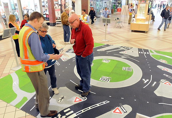 Bryant Ficek of TKDA Engineering talks to visitors about how to use a roundabout at a kiosk Saturday at the River Hills Mall. Pat Christman