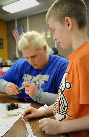Hilltop Elementary teacher Alexis Frischmon helps student Joseph Fiedler which a project in his STEM class.