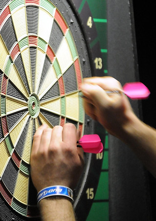 A player removes her darts from the board Saturday. Photo by Pat Christman