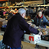 Pat Christman<br /> PACT volunteer Judy Becker helps distribute bread during the group's monthly food distribution Saturday at Goodrich Construction in Mankato.