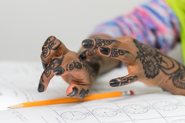 Najma Mohamed, 8, shows her tutor the henna on her hands while doing homework at the Islamic Center in St. Peter on Tuesday. Photo by Jackson Forderer