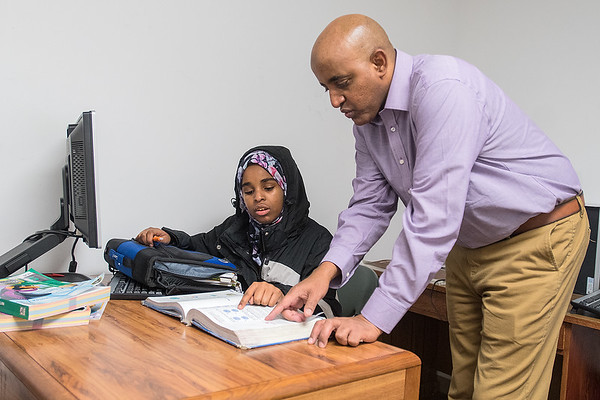 Affey Sigat (right), a student support specialist with St. Peter schools, helps Kadan Mohammed, 13, with her pre-algebra homework in a study room at the Islamic Center in St. Peter on Tuesday. Sigat said that he tutoring program has been open since last June and has 63 students in the after school program. Photo by Jackson Forderer