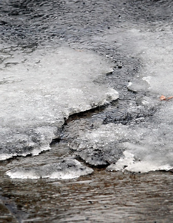 Rain and melting snow carve a river through ice Saturday.
