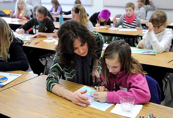 Artist Margie Keifer helps Emily Sowers, 8, with a watercolor painting during the Young Writers & Artists Conference Tuesday at Bethany Lutheran College.