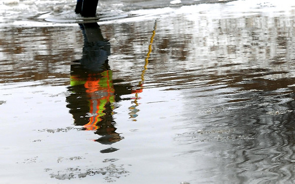 A North Mankato city employee, working to open frozen storm drains, is reflected in water flooding a frontage road off of Highway 169 North, near Blue Valley Sod. The southbound lanes of Highway 169 were closed from St. Peter to North Mankato Saturday afternoon after persistent rains caused water on the road and a mudslide.