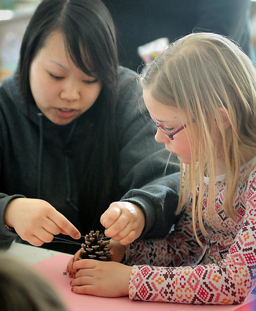 John Cross<br /> Minnesota State University student Gao Lee helps Callisto Shanafelt assemble a bird feeder during a Mankato Mavericks READ program Friday at the Elk's Learning Center at Rasmussen Woods. Another session of the free, nature-based event called Nature's Nook will be held there today from 9 a.m. to 11 a.m.