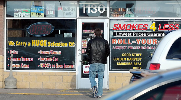 "A customer reads a hand written ""closed"" sign on the door of Smokes 4 Less in Mankato Tuesday evening."