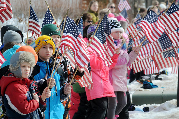 John Cross<br /> Hands over their hearts, school children watch as a funeral procession for fallen Marine Caleb Erickson passes by Monday in Waseca.
