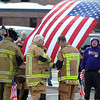 Pat Christman<br /> Waseca firefighters hang an American flag to the department's ladder truck Saturday.