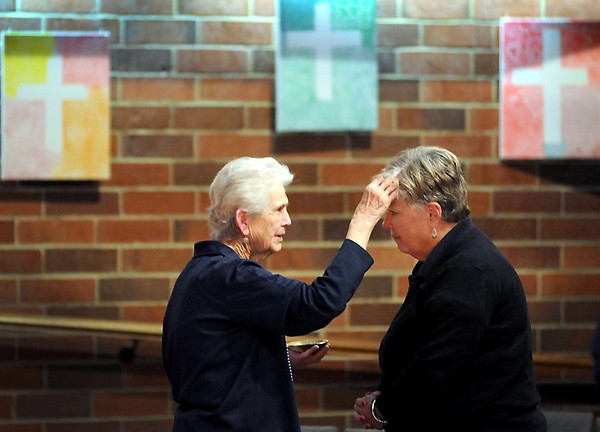 Pat Christman<br /> Centenary United Methodist Church director of caring ministries Jo Thomas places a cross of ashes on the forehead of Laura Samis during an Ash Wednesday service at the church. Ash Wednesday marks the beginning of the 40-day Lenten season for Christians that culminates on Easter Sunday.