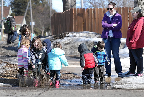 Pat Christman<br /> Tawnda Andrews, left, and Megan Schwichtenberg watch their children jump in a puddle during a walk along Main Street Thursday afternoon.