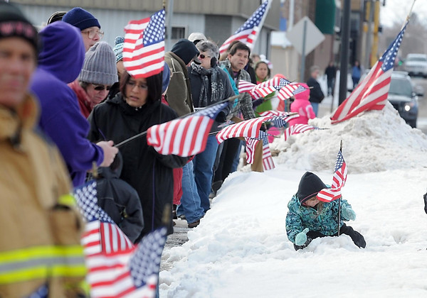 Pat Christman<br /> A young girl stands an American flag in a snowbank as people wait to see the hearse carring Marine Lance Cpl. Caleb Erickson's body Saturday.