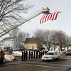 John Cross<br /> A hearse carrying the body of Marine Lance Cpl. Caleb Erickson passes beneath a giant flat suspended from fire truck ladder.