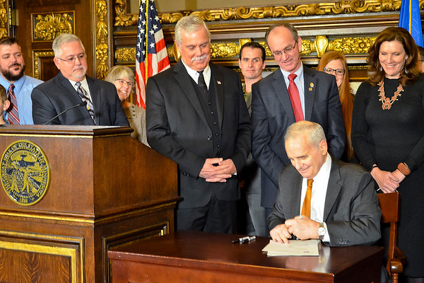 Gov. Mark Dayton, surrounded by area lawmakers and Madelia residents, signs into law $1.7 million in state aid toward Madelia's rebuilding efforts Friday morning. Photo by Trey Mewes