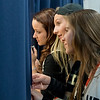 From left, Amanda Smith, Joie Weller and Katelyn McCabe peak through a curtain to watch the final moments of a basketball game before the Cleveland pep band played before the Clippers game against Mayer Lutheran. All three girls play saxophone in the pep band. Photo by Jackson Forderer