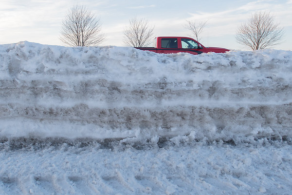 A truck passes by layers of snow along Victory Drive in Mankato. The predicted weekend blizzard will add yet another layer to the compacted snow. Photo by Jackson Forderer