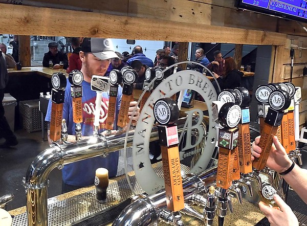 Curt VanAsten is reflected in a mirror as he taps one of Mankato Brewery's beers for a customer at the brewery's taproom. File photo